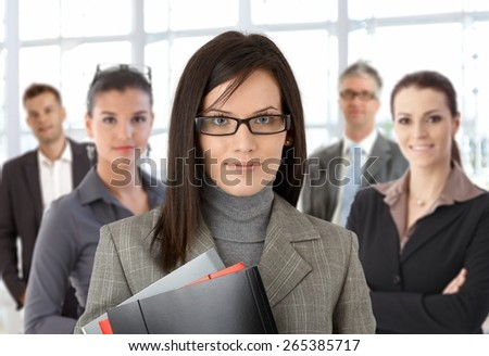 Closeup portrait of young businesswoman and team standing at office. - stock photo