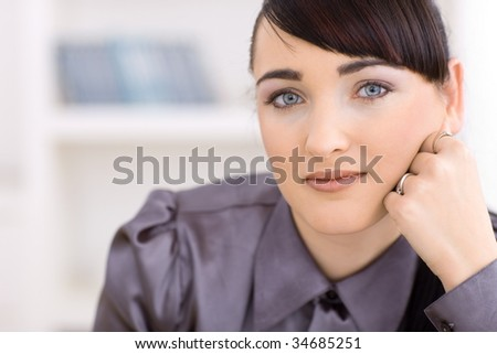 Closeup portrait of young businesswoman thinking, leaning on her hand. - stock photo