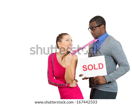 Closeup portrait of young couple, excited woman, happy to have man, pulling him away by tie, sad guy holding sold sign, isolated on white background. Human emotions facial expressions, feelings - stock photo