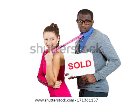 Closeup portrait of young couple, pair, excited woman, happy to have man, pulling him away by tie, sad guy holding sold sign, isolated on white background. Human emotions facial expressions, feelings - stock photo