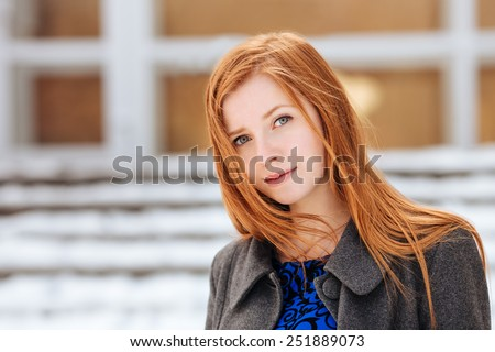 Closeup portrait of young cute redhead lady in blue dress and grey coat at winter outdoors - stock photo