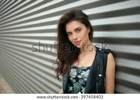 Closeup portrait of young fashionable brunette woman in black leather jacket posing outdoors against urban style background of metal strips - stock photo
