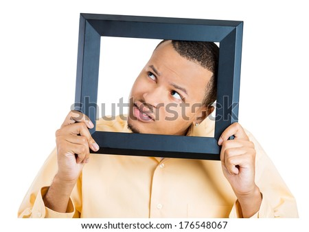 Closeup portrait of young funny face man sticking head in picture frame paranoid looking around, isolated on white background. Negative emotion facial expression feelings, situation,reaction. - stock photo