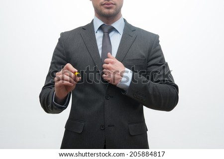 Closeup portrait of young handsome businessman holding marker and writing, drawing something in the air, isolated on white background - stock photo