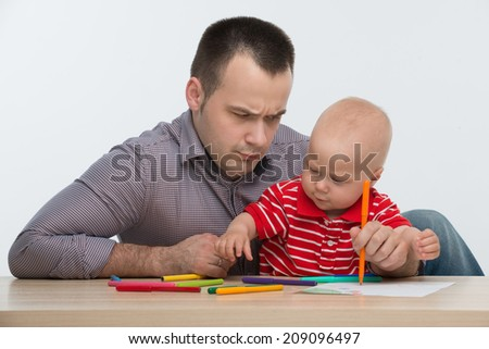 Closeup portrait of young handsome Caucasian father drawing with his cute toddler son, dad is confused, isolated on white - stock photo