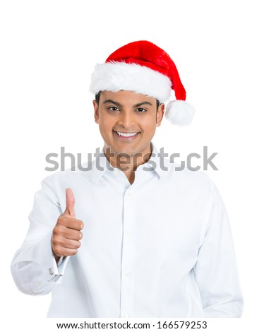 Closeup portrait of young handsome happy, smiling excited man in red santa hat giving thumbs up sign with fingers, isolated on white background. Positive emotion facial expressions and symbols  - stock photo