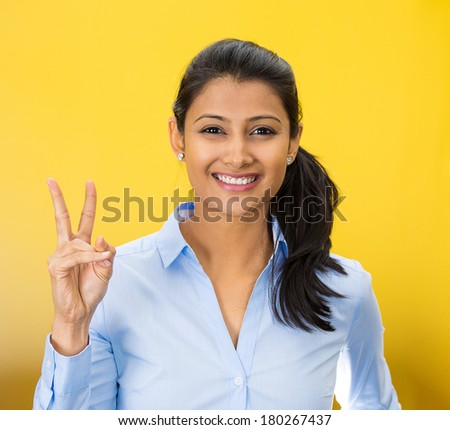 Closeup portrait of young happy smiling confident excited woman giving peace victory, two sign gesture, isolated on yellow background. Positive human emotion facial expression feeling symbol, attitude - stock photo