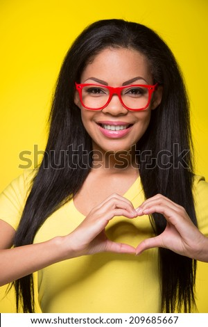 Closeup portrait of young happy woman. student wearing red glasses, showing heart sign - stock photo