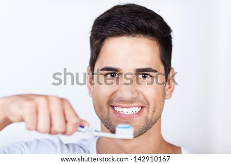 Closeup portrait of young man brushing teeth at home - stock photo
