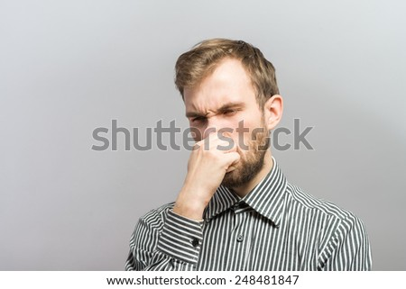 Closeup portrait of young man, disgust on face, pinches his nose, something stinks very bad smell, situation, asking is it you, isolated on gray background. Negative emotion facial expression feeling - stock photo