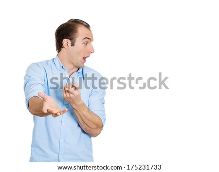 Closeup portrait of young man looking to side while pointing at you, surprised by something or someone, isolated on white background. Positive emotion facial expression feelings, attitude, reaction - stock photo