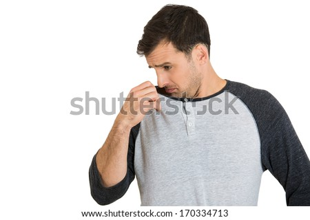 Closeup portrait of young man, smelling, sniffing his armpit, something stinks, very bad, foul odor situation, Isolated on white background Negative emotion, facial expression, feeling - stock photo
