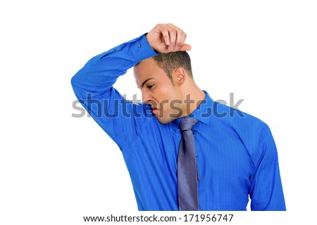Closeup portrait of young man, smelling, sniffing his wet armpit, something stinks, very bad, foul odor situation, isolated on white background. Negative human emotions, facial expressions, feelings - stock photo