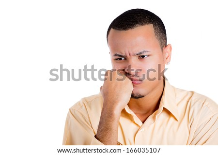 Closeup portrait of young man thinking daydreaming deeply about something with chin on hand fist looking downwards, isolated on white background, space to left. Emotion facial expressions feelings - stock photo