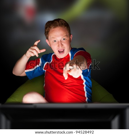 Closeup portrait of young man wearing sportswear fan of football team is watching tv and rooting for his favorite team. Sitting on beanbag alone at night. Light from television. - stock photo
