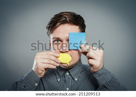 Closeup portrait of young man with a piece of paper covering his mouth and eyes on gray background - stock photo