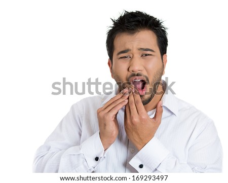 Closeup portrait of young man with tooth ache problem about to cry from oral pain touching outside mouth with hand, isolated white background. Negative emotion facial expression feeling - stock photo