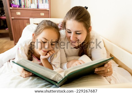 Closeup portrait of young mother and daughter lying in bed and viewing photo album - stock photo