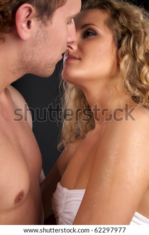 Closeup portrait of young naked couple in love over black background - stock photo