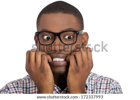 Closeup portrait of young nerdy, unhappy, scared man, student with big glasses biting nails, looking away with a craving for something, anxious, worried, isolated on white background. Face expression - stock photo