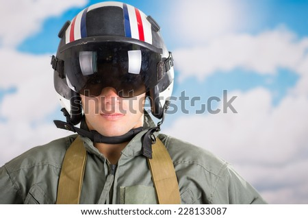 closeup portrait of young pilot wearing helmet with a sky background - stock photo
