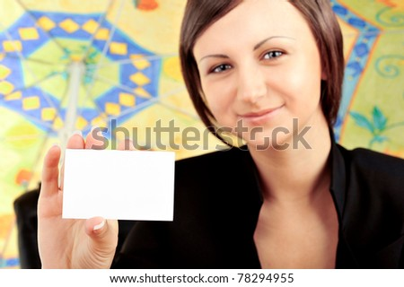 Closeup portrait of young pretty woman holding business card on foreground. Sitting relaxed under beach umbrella. Vacation concept - stock photo