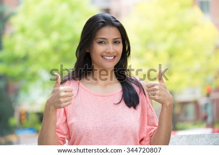 Closeup portrait of young pretty woman in pink shirt with two thumbs up sign gesture, isolated outdoors background. Positive emotion facial expression feelings, signs and symbols, body language - stock photo