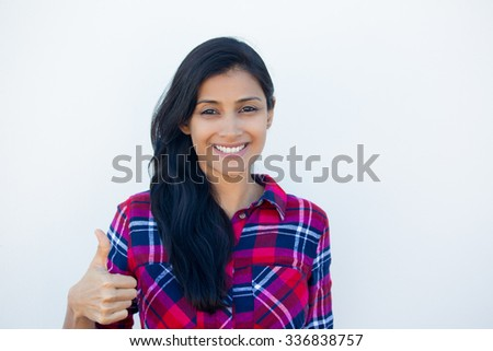 Closeup portrait of young pretty woman with one thumbs up sign gesture, plaid red shirt, isolated white wall background. Positive emotion facial expression feelings, signs and symbols, body language - stock photo