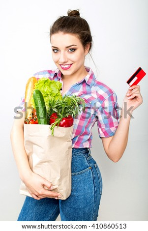 Closeup portrait of young smiling woman holding paper sack with fresh food and credit card isolated over white - stock photo