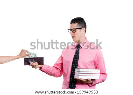 Closeup portrait of young student man holding books in one hand and wallet in the other, looking distressed, disgusted while someone takes money from him, isolated on white background. Education value - stock photo