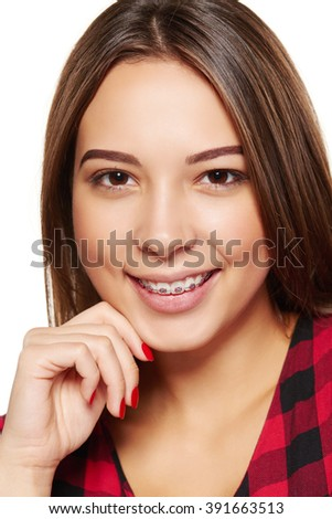 Closeup portrait of young teen female smiling with braces on her teeth - stock photo