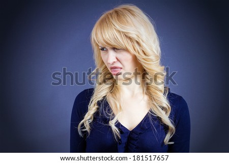 Closeup portrait of young woman disgusted with someone, something, looking to side, sticking out tongue isolated dark blue background. Negative emotion facial expression feelings, reaction, perception - stock photo