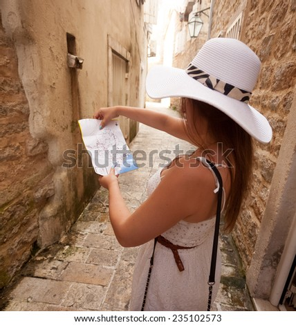 Closeup portrait of young woman looking at map on old narrow street - stock photo