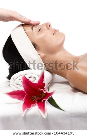 Closeup portrait of young woman receiving facial massage, laying eyes closed, side view. - stock photo