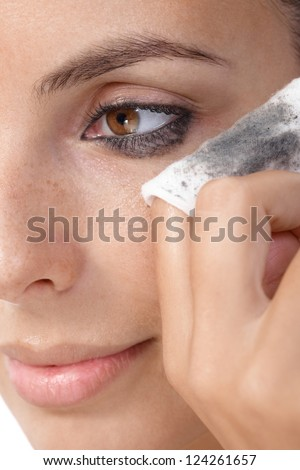 Closeup portrait of young woman removing eye makeup, by cotton pad. - stock photo