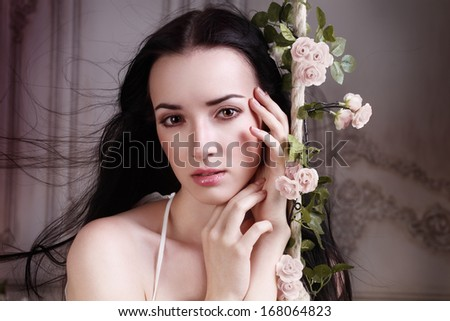 closeup portrait of young woman with good skin holding her hand near her hands and looking to the camera - stock photo