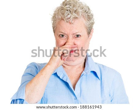 Closeup portrait old lady, senior executive, grandmother, disgust on her face, pinching nose something stinks, displeased with situation, isolated white background. Interpersonal conflict - stock photo