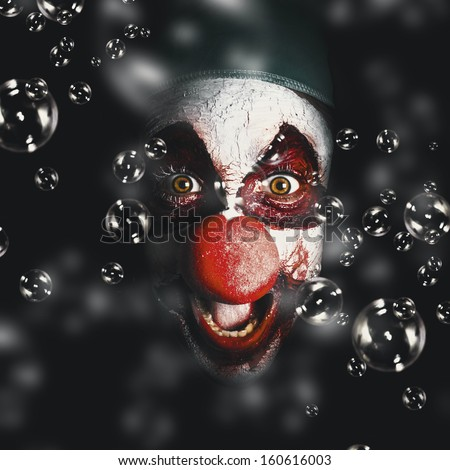 Closeup portrait on a scary horror circus clown laughing with evil smile among birthday party bubbles. Crazy celebration - stock photo