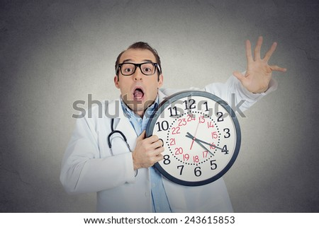 Closeup portrait overwhelmed, busy, unhappy male health care professional, funny looking doctor guy holding wall clock running out of time exhausted isolated grey wall background. Healthcare reform - stock photo