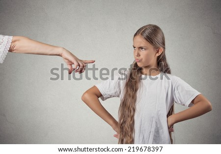Closeup portrait parent pointing at child in white t-shirt scolding go to room grounded for misbehaving while kid is looking disobedient hands on hips, isolated grey wall background. Negative emotion - stock photo