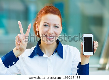 Closeup portrait, photo attractive happy, smiling young business woman presenting, holding smartphone screen, giving victory sign isolated background corporate office windows. Positive face expression - stock photo