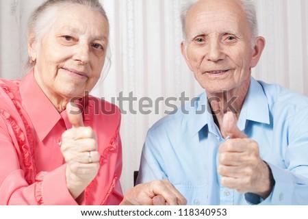 Closeup portrait positive elderly couple happy, thumbs-up gesture - stock photo