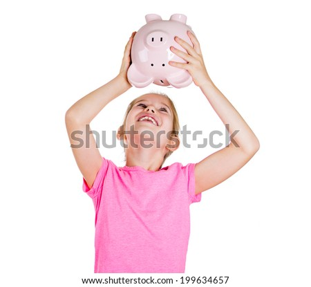 Closeup portrait pretty, smiling, happy,  little girl in pink t-shirt, shaking her piggy bank, trying to figure out how much money she has saved, isolated white background in studio. Face expressions - stock photo