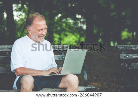 Closeup portrait, regular senior mature man in white shirt happily typing away, browsing digital computer laptop, isolated background of sunny outdoor, green trees nature background. Leisure time - stock photo