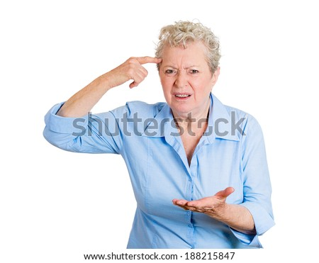 Closeup portrait rude, difficult angry senior mature woman, gesturing with finger against temple, are you crazy? Isolated white background. Negative human emotion, facial expression, feeling, attitude - stock photo