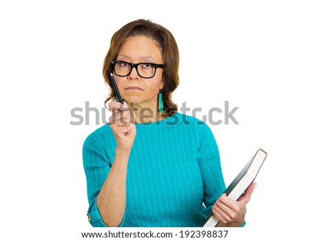 Closeup portrait senior, elderly female teacher holding book, pen, looking very serious, unhappy, grumpy, pointing at you isolated white background. Human emotion, facial expression. Education concept - stock photo