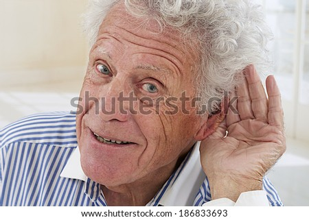 Closeup portrait, senior man, hard of hearing, placing hand on ear asking someone to speak up - stock photo