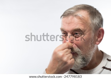 Closeup portrait, senior mature man, disgust face, pinch nose, looks funny, something stinks, very bad smell, isolated white background. Negative emotion, facial expression, feeling reaction - stock photo