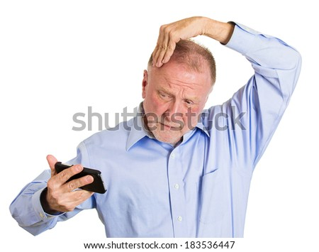 Closeup portrait senior mature man feeling head, surprised he is losing hair, receding hairline or seeing bad news on cellphone, isolated white background. Negative facial expressions, emotion feeling - stock photo