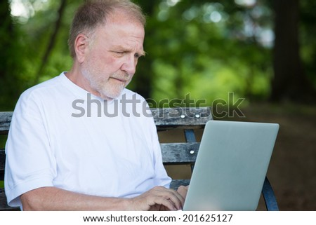 Closeup portrait, senior mature man in white shirt typing away, browsing digital computer laptop, isolated background of sunny outdoor, green trees nature background - stock photo